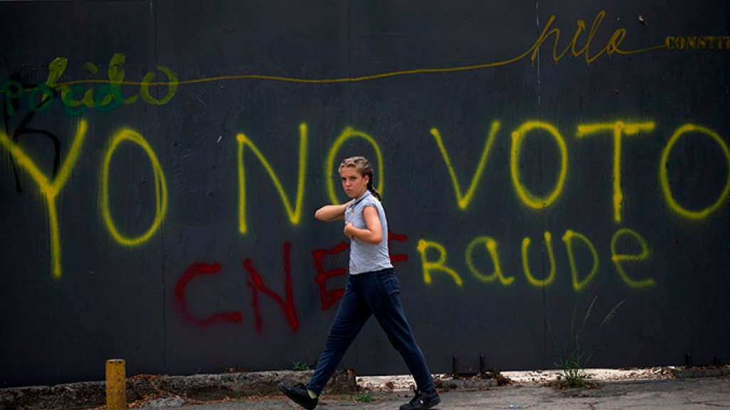 "A Venezuelan walks past a wall with graffiti that reads ""I won't vote."""
