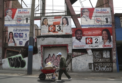 A man walks by campaign posters in Lima. (AP)