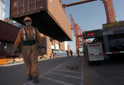 Workers unload a container vessel docked in Ensenada, Mexico.
