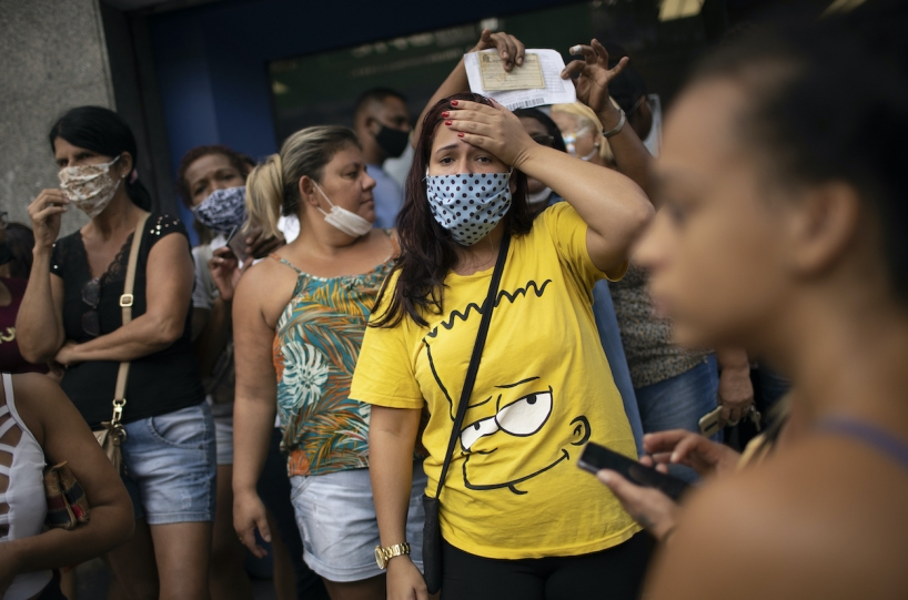 Women in Rio de Janeiro wait outside a government-run bank having technical problems to distribute their aid money. (AP)
